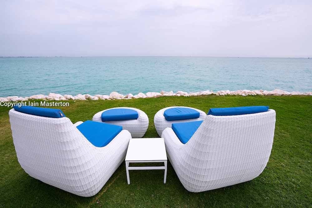Two white sun loungers beside the sea in Doha Qatar