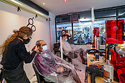 People get their hair cut at a hairdresser in Soho, central London on Tuesday, April 13, 2021. Millions of people in England will get their first chance in months for haircuts, casual shopping and restaurant meals on Monday, as the government takes the next step on its lockdown-lifting road map. (Photo/ Vudi Xhymshiti)