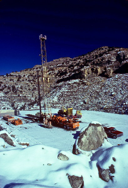 A workover oil rig with snow in the mountains of Utah in winter.