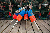 colorful, intimate composition of lobster traps and buoys found on a fishing pier in Bass Harbor, Maine