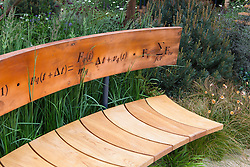 Curved bench seat decorated with mathematical symbols cut into band of copper forming back. The Winton Beauty of Mathematics Garden, Chelsea Flower Show 2016