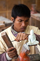 "Sculptor at Artisans d'Angkor - a group trained by the Chantiers Écoles de Formation Professionnelle. Located in Siem Reap, Cambodia, with two training schools. An initiative of the National Cambodian Institutions, the French Foreign Ministry and the European Union, Chantiers Ecoles de Formation Professionnelle provides unschooled rural youth with free vocational training programs, while Artisans d'Angkor provides them a professional, economic and social integration into providing a service for their locale. Its objectives are to support and promote Khmer art and culture, educating local youth, and provide jobs to youth interested in traditional crafts. The Artisan's centre, established to perpetuate the art and culture of the World Heritage Site of Angkor through training the present generation of local youth in the disciplines of metal working, silk weaving, and wood and stone carving had the distinction of the artisans of the institute won the award ""Seal of Excellence for Handicrafts"" in a competition organized by UNESCO."