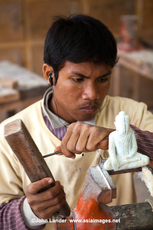 """Sculptor at Artisans d'Angkor - a group trained by the Chantiers Écoles de Formation Professionnelle. Located in Siem Reap, Cambodia, with two training schools. An initiative of the National Cambodian Institutions, the French Foreign Ministry and the European Union, Chantiers Ecoles de Formation Professionnelle provides unschooled rural youth with free vocational training programs, while Artisans d'Angkor provides them a professional, economic and social integration into providing a service for their locale. Its objectives are to support and promote Khmer art and culture, educating local youth, and provide jobs to youth interested in traditional crafts. The Artisan's centre, established to perpetuate the art and culture of the World Heritage Site of Angkor through training the present generation of local youth in the disciplines of metal working, silk weaving, and wood and stone carving had the distinction of the artisans of the institute won the award """"Seal of Excellence for Handicrafts"""" in a competition organized by UNESCO."""