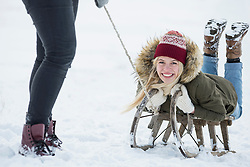 Two teenage girls with slide in snowy landscape in winter, Bavaria, Germany