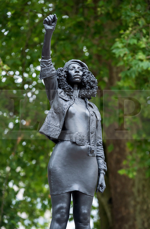 """© Licensed to London News Pictures; 15/07/2020; Bristol, UK. People view and photograph a new statue of a black lives matter protestor has been placed on the plinth from where the statue of slave trader Edward Colston was pulled down with ropes and thrown into Bristol docks on 07 June during an All Black Lives/Black Lives Matter protest that made headlines around the world. The new sculpture is titled """"A Surge of Power (Jen Reid) 2020"""" by artist Marc Quinn and is made of black resin and steel and was put up around dawn this morning without any permission from Bristol City council. Jen Reid was at the previous protest on 07 June which was in protest for the memory of George Floyd, a black man who was killed on May 25, 2020 in Minneapolis in the US by a white police officer kneeling on his neck for nearly 9 minutes. The killing of George Floyd has seen widespread protests in the US, the UK and other countries. Photo credit: Simon Chapman/LNP."""