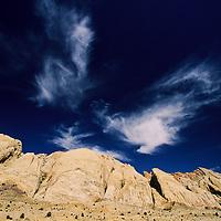 Wispy clouds break up the blue sky over sagebrush and sandstone bluffs, San Raphael Swell, Utah