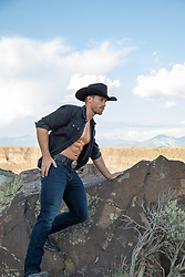 cowboy with open shirt on a rock overlooking The Rio Grande