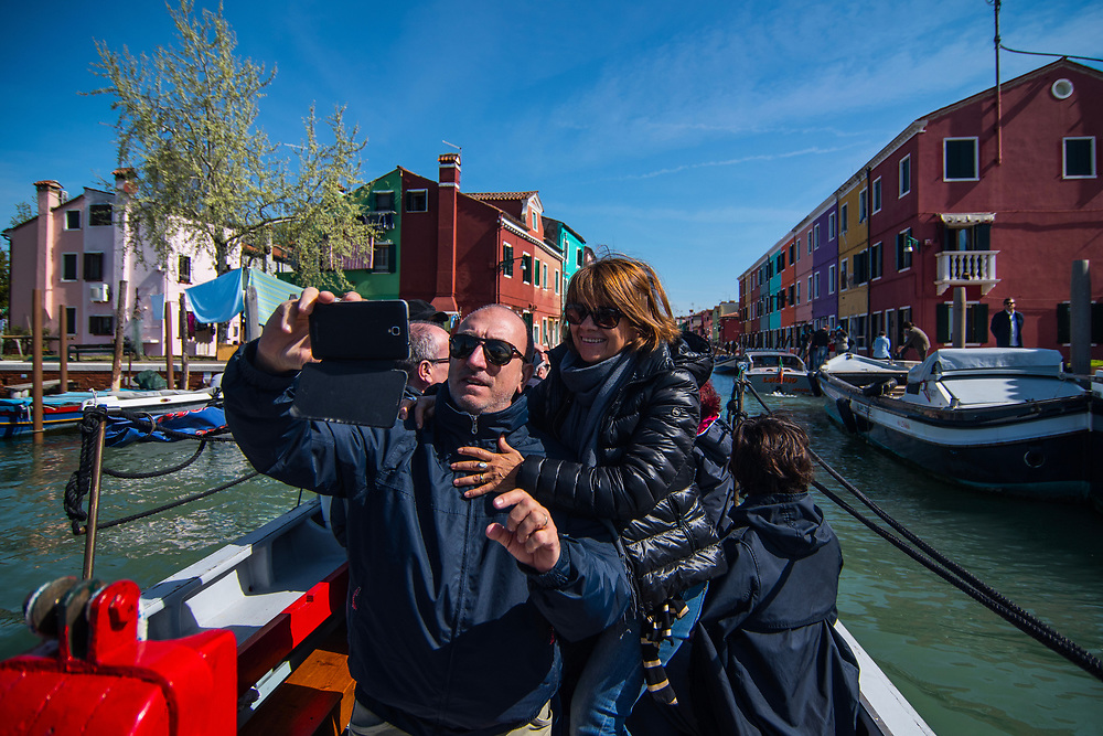 VENICE, ITALY - APRIL 2018. <br /> Tourists takes pictures the passage through Burano, before reaching Emiliano, a moecante (crabs fisherman), that will show them the traditional fishing of moeche. The island of Burano is a pearl of the Venetian lagoon. It is well known for its colored houses and the traditional art of making laces, that are, also, a Unesco heritage.