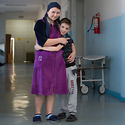 CAPTION: Kirill's stepmother explains that he was born with a complete bilateral cleft lip and palate. This is the most difficult type of cleft to correct, and he is currently only part way through a series of multiple operations that were needed to correct it. LOCATION: Volgograd City Hospital #1, Volgograd, Russia. INDIVIDUAL(S) PHOTOGRAPHED: Tatiana Fedorenko (left) and Kirill Fedorenko (right).