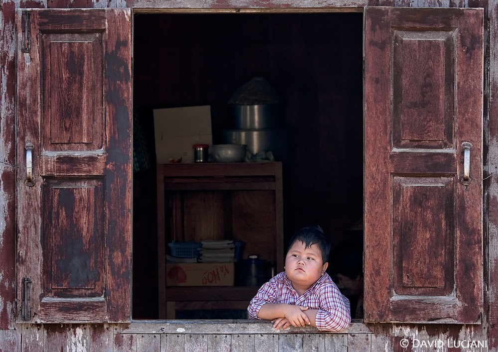 A boy looking out the window as we passed his house under a hot midday sun.