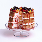 Studio photograph of a three tiered angel food layer cake with fruit toppings and fruit juice drizzling down the sides. sitting on a white table
