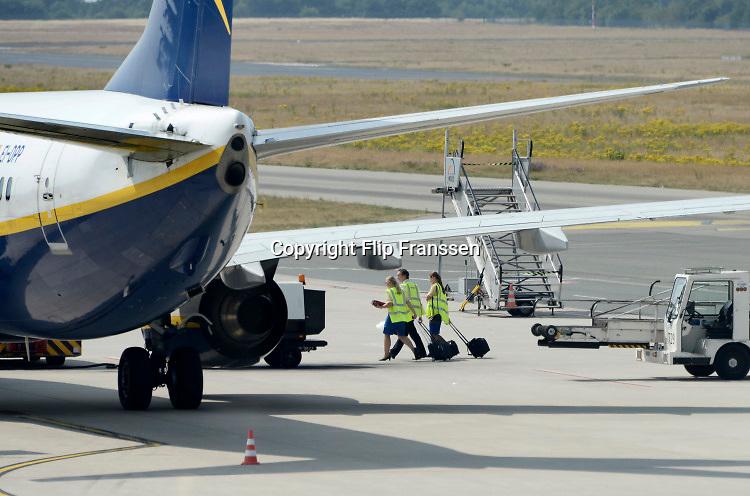 Duitsland, Weeze, 22-7-2018Bemanning van een vliegtuig van Ryanair loopt naar het toestel. In het vakantieseizoen is het erg druk op vliegveld Weeze. Vlak over de grens bij Nijmegen ligt het regionaal vliegveld Niederrhein, Weeze, wat uitgegroeid is tot een belangrijke regionale luchthaven en als thuisbasis fungeert voor prijsvechter, chartermaatschappij Ryanair. In de regio bevindt zich ook vliegveld Dusseldorf. Naast passagiersvervoer wordt er veel luchtvracht vervoerd. Foto: Flip Franssen