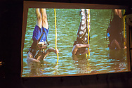 Merrick, New York, USA. June 11, 2017.  American Grit TV show contestant CHRIS EDOM (at left in blue swim trunks during show), 48, of Merrick, hosts Viewing Party for Season 2 premiere. Edom family's relatives and neighbors watched Episode 1 of the Fox network TV show on large screen in their backyard. Edom was the last contestant picked for a team.