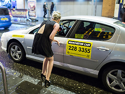 © Licensed to London News Pictures . 21/12/2013 . Manchester , UK . A woman gets in to a cab . Christmas revellers out in the rain in Manchester on Mad Friday , the last Friday night before Christmas which is typically one of the busiest nights of the year for police and ambulance crews . Photo credit : Joel Goodman/LNP