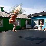 Toustrup Mark Community,  Sporup, Denmark, June, 5, 2010. Lea jumps in the garden. Toustrup Mark, 30 km west of Aarhus, has 25 apartments and a total of 70 inhabitants.<br /> The community is spread over 50,000 m2 of land with a forest, a soccer field, a volleyball court and a small lake with private beach.<br /> It seems that living in co-housing is very educational for children who can learn from an early age to interact within a social system extended.