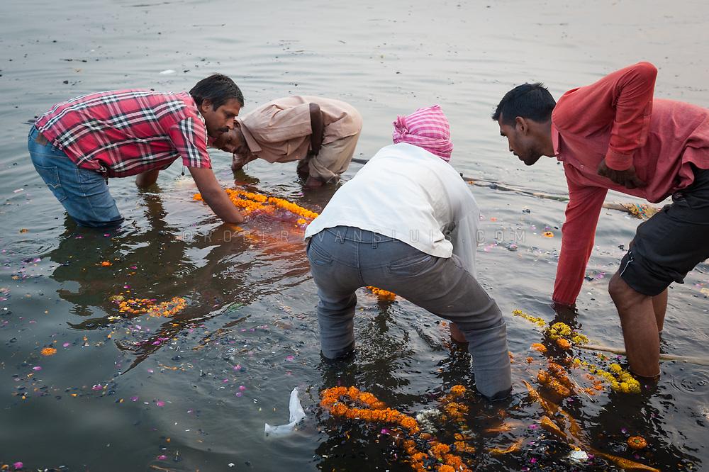 Family members dip the decorated body into the Ganges River at Manikarnika cremation ground, Varanasi, India. Photo ©robertvansluis.com