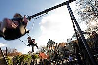 """9 Novembre, 2008. Brooklyn, New York.<br /> <br /> Dei bambini giocano sull'altalena del parco giochi di Prospect Park a Park Park Slope, Brooklyn, NY. Park Slope, spesso definito dai newyorkesi come """"The Slope"""", è un quartiere nella zona ovest di Brooklyn, New York, e confinante con Prospect Park.  Park Slope è un quartiere benestante che ha il maggior numero di nascite, la qualità della vita più alta e principalmente abitato da una classe media di razza bianca. Per questi motivi molte giovani coppie e famiglie decidono di trasferirsi dalle altre municipalità di New York a Park Slope. Dal punto di vista architettonico, il quartiere è caratterizzato dai brownstones, un tipo di costruzione molto frequente a New York, e da Prospect Park.<br /> <br /> ©2008 Gianni Cipriano for The New York Times<br /> cell. +1 646 465 2168 (USA)<br /> cell. +1 328 567 7923 (Italy)<br /> gianni@giannicipriano.com<br /> www.giannicipriano.com"""