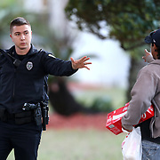 A police officer instructs a resident to return to the safe zone as agents search for suspect Markeith Loyd at the Tzadik Brookside Apartments on January 9 2017 in Orlando, Florida. Loyd shot an Orlando Police officer earlier in the day at a local Walmart, the officer has since died.  (Alex Menendez via AP)