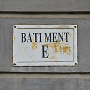 A sign for Batiment E o (or cell block E) in Hoa Lo Prison. Hoa Lo Prison, also known sarcastically as the Hanoi Hilton during the Vietnam War, was originally a French colonial prison for political prisoners and then a North Vietnamese prison for prisoners of war. It is especially famous for being the jail used for American pilots shot down during the Vietnam War.