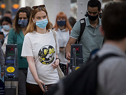 © Licensed to London News Pictures. 05/07/2021. London, UK. Members of the public are seen wearing face masks as they disembark a train at Paddington Station in West London. Later today the Prime Minister Boris Johnson will announce a final lifting of Covid-19 regulations on July 19th. Photo credit: Ben Cawthra/LNP