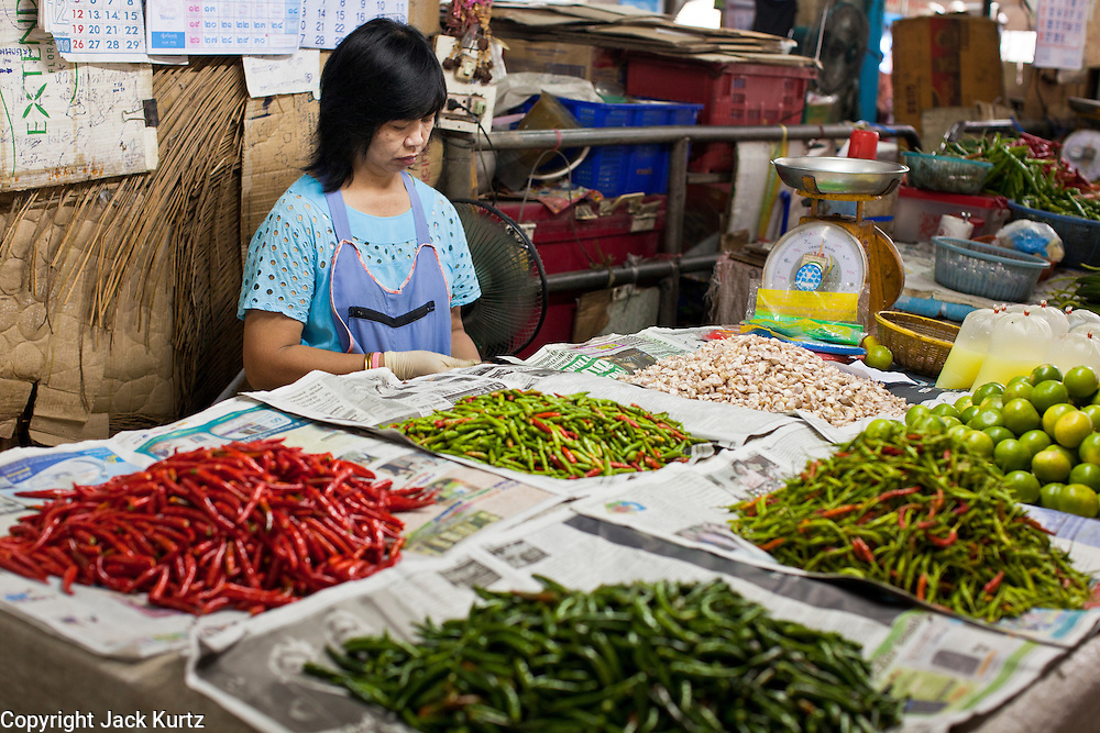 24 JUNE 2011 - CHIANG MAI, THAILAND: A woman sells chilis and limes in the market in Chiang Mai, Thailand.  PHOTO BY JACK KURTZ