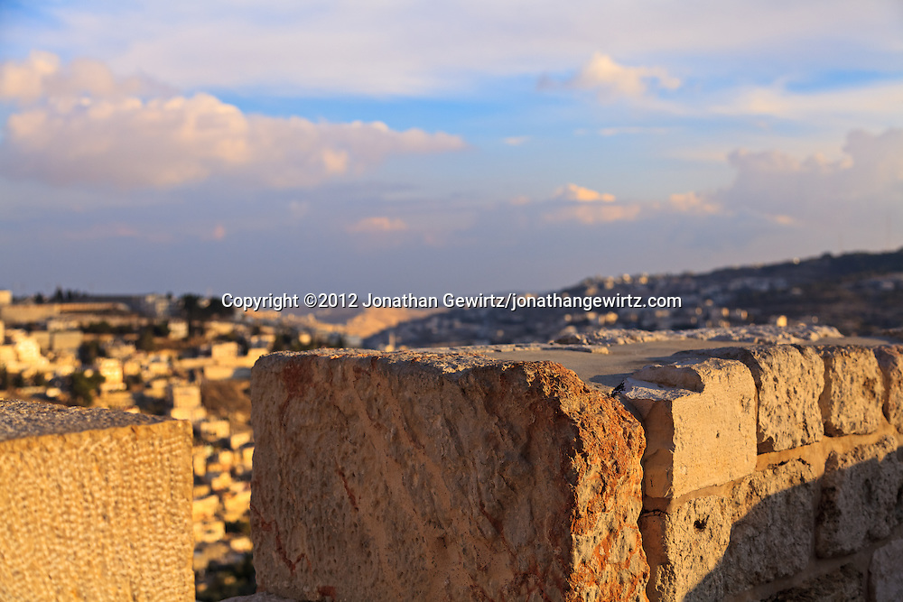 Closeup view of a battlement on the top of one of the exterior walls of the Old City of Jerusalem. The village of Silwan is visible in the background.