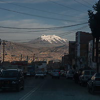 Snow-capped mountains of the altiplano are the backdrop for a street scene in La Paz