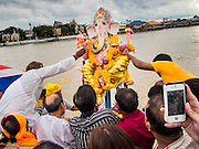 "15 SEPTEMBER 2013 - BANGKOK, THAILAND: Hindus in Bangkok push statues of Ganesha into the Chao Phraya River on the last day of Ganesha Chaturthi celebrations at Shiva Temple in Bangkok. Ganesha Chaturthi is the Hindu festival celebrated on the day of the re-birth of Lord Ganesha, the son of Shiva and Parvati. The festival, also known as Ganeshotsav (""Festival of Ganesha"") is observed in the Hindu calendar month of Bhaadrapada. The festival lasts for 10 days, ending on Anant Chaturdashi. Ganesha is a widely worshipped Hindu deity and is revered by many Thai Buddhists. Ganesha is widely revered as the remover of obstacles, the patron of arts and sciences and the deva of intellect and wisdom. The last day of the festival is marked by the immersion of the deity, which symbolizes the cycle of creation and dissolution in nature.  In Bangkok, the deity (statue) was submerged in the Chao Phraya River.         PHOTO BY JACK KURTZ"