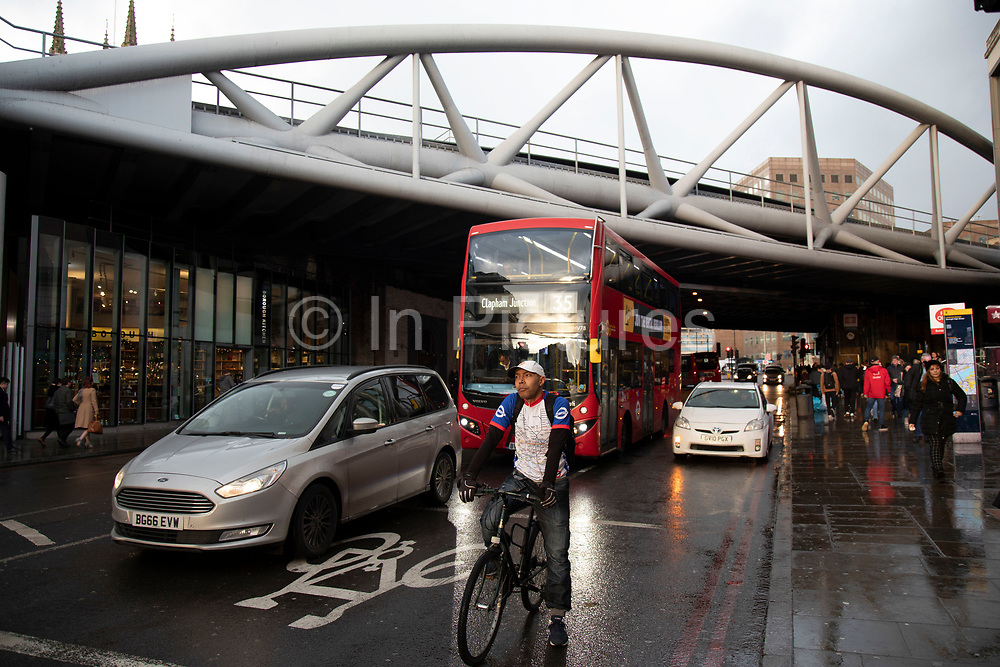 Cyclist waiting at traffic lights on a wet day at Borough / London Bridge on 27th November 2019 in London, England, United Kingdom. This area got its name from when it was the only borough outside the City of London. Borough High Street is the areas main street, and it is famous for Borough Market, Guys Hospital and London Bridge station.