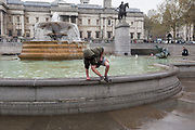 After scavenging for thrown coins in the fountains of Trafalgar Square, a man climbs out of the freezing chemically-treated water, on 9th April 2019, in London, England.