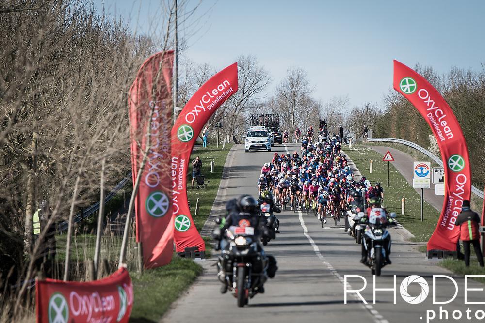 peloton rolling into De Moeren<br /> <br /> Oxyclean Classic Brugge-De Panne 2021 (WE/1.WWT) - Belgium<br /> 1 day race from Brugge to De Panne (159km)<br /> <br /> ©RhodePhoto