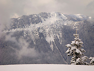 The Mount Tahoma Trails south district with High Hut Ridge and High Hut at the peak of the ridge is seen across the Nisqually River Valley with High Hut ridge prominent on the right and Griffin Mountain on the left.  Fresh late winter snow blankets the mountains from a recent storm. The Mount Tahoma Trails is a non-profit hut-to-hut crosscountry ski and snowshoe trail system on the Tahoma State Forest and private lands in the Washington state Cascade Mountain Range near Mount Rainier.