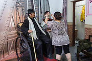 A Chinese man dresses in costume at a photo studio in Yu Gardens bazaar Shanghai, China