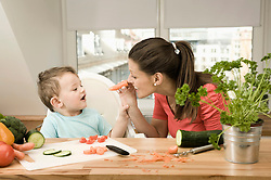 Mother and son preparing vegetables in kitchen, smiling