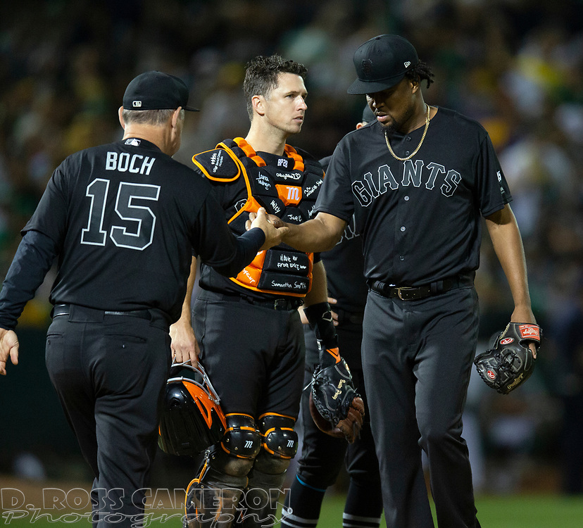 San Francisco Giants manager Bruce Bochy (15) takes the ball from relief pitcher Jandel Gustave, right, during the seventh inning of a Major League Baseball game against the Oakland Athletics Saturday, Aug. 24, 2019 in Oakland, Calif. (D. Ross Cameron/SF Chronicle)