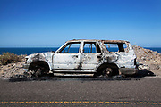 Image of a burned out car roadside in Baja with the Sea of Cortez in the background, Baja California Sur, Mexico by Randy Wells