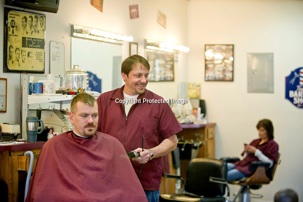 Marty Taylor, right, owner of Taylor's Barbershop, laughs while cutting the hair of Jim Niederriter, of Altus, Ark., on Friday, Nov. 12, 2011, in his store in Ozark, Ark. (Photo by Beth Hall)