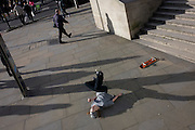 Pedestrians ignore a young skateboarder flying through the air during his acrobatic jump down steps.