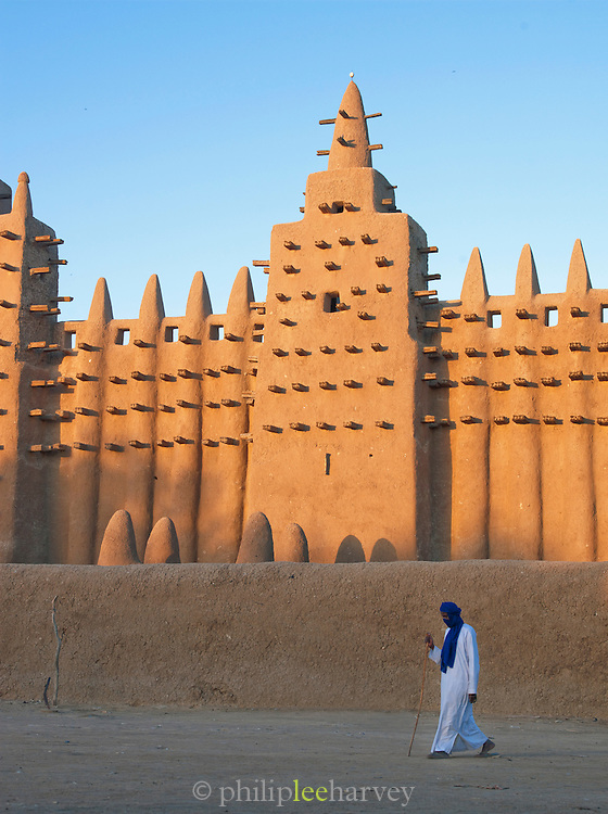A man walks outside the Great Mosque of Djenné, the worlds largest mud built structure and UNESCO heritage site, in the early morning at Djenné, Mali