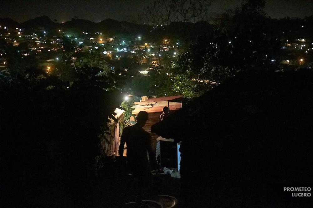 Juan Martinez, de 17 años, un joven deportado, evita salir en la calle por las noches. Su vida está en peligro. Retratado afuera de su casa en lo alto de un cerro, sus movimientos personales están limitados a la luz de día, desde que regresó deportado a San Pedro Sula. (Prometeo Lucero)