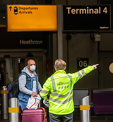 © Licensed to London News Pictures. 10/03/2020. London, UK. A passengers in a mask is directed by Heathrow staff at Terminal 4 where flights to Italy continue to run as British Airways cancels all flights to and from Italy over fears of the Coronavirus disease. Photo credit: Alex Lentati/LNP