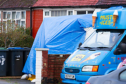 A forensics tent lies behind an ice cream van at no 97  as police guard the scene on St Joseph's Road in Enfield, North London where a man was shot and died at the scene on the evening of December 18th . London, December 19 2018.