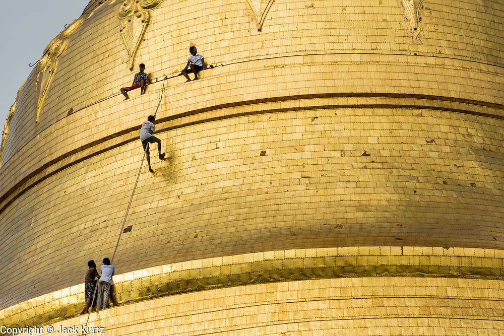 15 JUNE 2013 - YANGON, MYANMAR: Boys climb up the side of Shwedagon Pagoda to leave an offering at the top of the Pagoda. Shwedagon Pagoda is officially known as Shwedagon Zedi Daw and is also called the Great Dagon Pagoda or the Golden Pagoda. It is a 99 meter (325 ft) tall pagoda and stupa located in Yangon, Burma. The pagoda lies to the west of on Singuttara Hill, and dominates the skyline of the city. It is the most sacred Buddhist pagoda in Myanmar and contains relics of the past four Buddhas enshrined: the staff of Kakusandha, the water filter of Koṇāgamana, a piece of the robe of Kassapa and eight strands of hair from Gautama, the historical Buddha. Burmese believe the pagoda was established as early ca 540BC, but archaeological suggests it was built between the 6th and 10th centuries. The pagoda has been renovated numerous times through the centuries. Millions of Burmese and tens of thousands of tourists visit the pagoda every year, which is the most visited site in Yangon. PHOTO BY JACK KURTZ