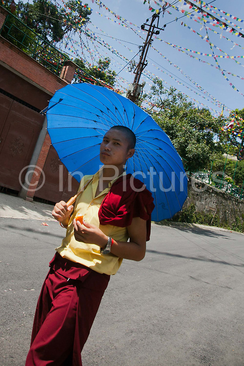 An ice cream eating young monk leaving the Swayambhunath temple complex, also called the Monkey Temple.