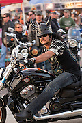 A leather clad biker with animal horns on his helmet cruises down Main Street during the 74th Annual Daytona Bike Week March 8, 2015 in Daytona Beach, Florida. More than 500,000 bikers and spectators gather for the week long event, the largest motorcycle rally in America.
