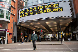 © Licensed to London News Pictures. 16/10/2020. Manchester, UK. A man walks past a large digital sign on Market Street, Manchester, urging residents to 'Act Now'. Manchester is on the verge of a Tier 3 lockdown. Photo credit: Kerry Elsworth/LNP