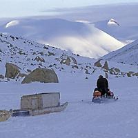 BAFFIN ISLAND, Nunavut, Canada. Inuit hunter, snowmobile and kamatik sled in Stewart Valley.