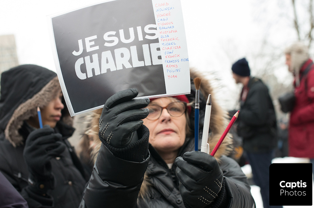 """Hundreds of people gathered at Confederation Park in Ottawa with French flags and signs reading """"Je Suis Charlie"""". The rally was organized to show solidarity with Parisians following the Charlie Hebdo shooting. January 11, 2015."""