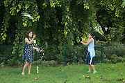 2 Young female teens, spinning Pois in a park
