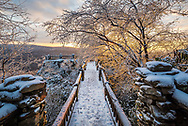 The path leading to the main overlook at Coopers Rock State Forest in West Virginia is covered in snow and ice, the sun providing a warm backlight against the ice covered trees.